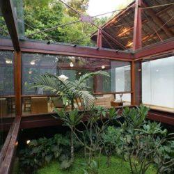 Com jardim centralizado da casa em metálicas